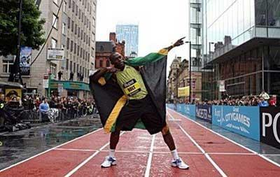 Olympic sprinter Usain Bolt celebrates after winning the final of the 150 metres sprint at the Citygames in Manchester. Bolt ran the fastest ever 150m on Sunday in a street race held in a chilly and windy Manchester City Centre.(AFP/Andrew Yates)