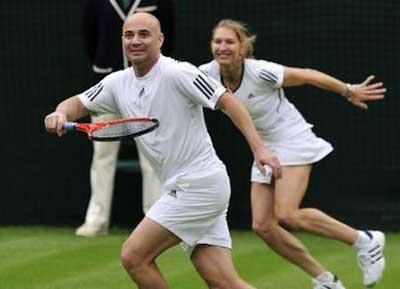 Andre Agassi of the U.S. and Germany's Steffi Graf react during their mixed doubles match against Tim Henman and Kim Clijsters under the newly completed Centre Court roof at Wimbledon in London in this May 17, 2009 file photo. As a seven-times champion, Graf thought she knew every nook and cranny of Wimbledon and considered it to be her personal backyard. Looking forward to a trip down memory lane, she jumped at the chance of teaming up with husband Agassi to play in an exhibition event to mark the unveiling of the new retractable roof over Centre Court. To match feature TENNIS/GRAF REUTERS/Kieran Doherty/Files (BRITAIN SPORT TENNIS SOCIETY)