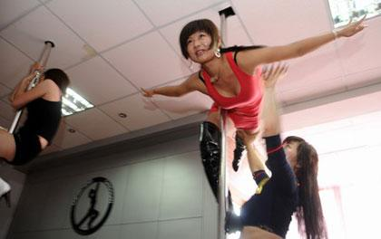 A woman gets instruction at a pole dancing class, the latest aerobic trend, in Luoyang, central China's Henan province, Tuesday June 9, 2009. Pole dancing is nudging its way into the mainstream Chinese exercise market with growing numbers of gyms and dance schools offering classes. [CFP]