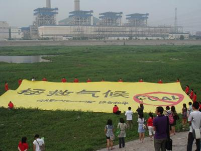 Greenpeace China volunteers stand at the Yongding River bank in western Beijing, holding a yellow flag on which the Chinese characters read: Save the climate. The environmental group urged China's top power companies to help move the country away from coal and to cut carbon dioxide emissions by aggressively improving energy efficiency and developing renewable energy sources.