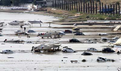 Partially submerged cars are seen next to boats after heavy rains flooded Silivri, a town some 70 km (44 miles) from Istanbul September 8, 2009. Flash floods triggered by torrential rains killed six people and left swaths of lands in northwestern Turkey awash Tuesday. [Agencies]