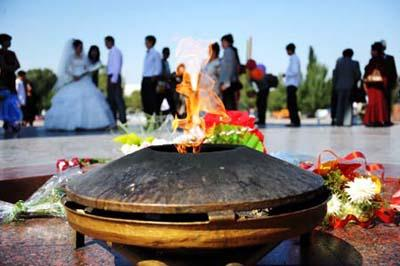 Photo taken on Sept. 12, 2009 shows the eternal flame at the Victory Square in Bishkek, capital of Kyrgyzstan. It is a tradition for many Kyrgyzstan's newly-married couples to come to the Victory Square to pray for happiness in their life.(Xinhua/Sadat)