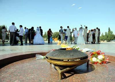 The eternal flame is seen with the background of a newly-married couple setting free doves at the Victory Square in Bishkek, capital of Kyrgyzstan, Sept. 12, 2009. It is a tradition for many Kyrgyzstan's newly-married couples to come to the Victory Square to pray for happiness in their life.(Xinhua/Sadat)