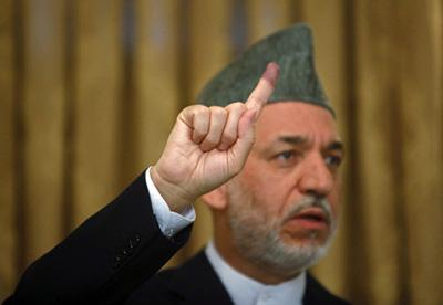 File photo shows that Afghan President Hamid Karzai holds up his inked stained finger as he gestures during a news conference on election day in Kabul August 20, 2009. (Xinhua/Reuters Photo)