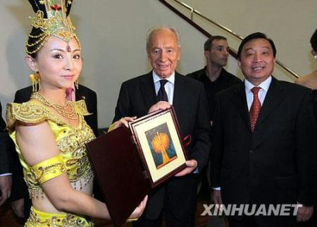 "Tai Lihua (L), head of China Disabled People's Performing Art Troupe, presents a gift to Israeli President Shimon Peres before the opening of ""Experience China in Israel"" cultural event formally in Tel Aviv Opera House, Oct. 17, 2009.(Xinhua Photo)"